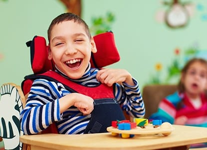 Laughing young boy in wheelchair