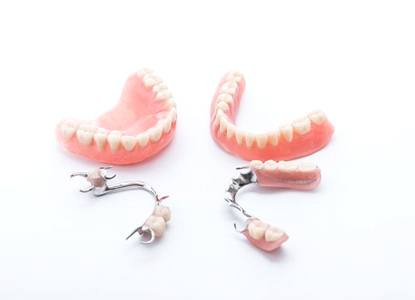full and partial dentures against white background