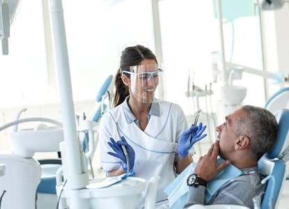 A dentist speaking with a dental patient.