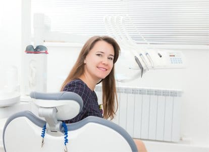 Calm dental patient turning to look behind dental chair