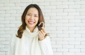 Woman standing in front of a white brick wall wearing a white sweater and smiling as she holds an Invisalign tray
